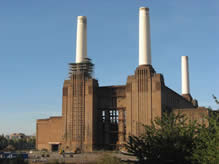 white pianted power station chimneys against a blue sky