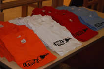 various coloured Unlock T shirts laid out on a table